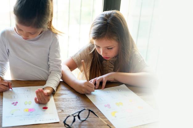 Małe dziewczynki uczą się w domu podczas pandemii koronawirusa