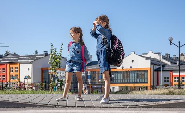 Małe dziewczynki, uczennice podstawówki po szkole, w drodze do domu.