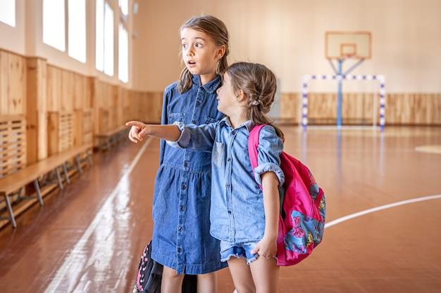 Małe dziewczynki uczennice szkoły podstawowej z plecakami po szkole w szkolnej sali gimnastycznej