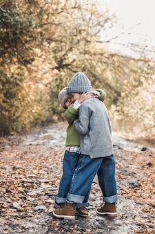 Małe dziewczynki uśmiechają się i cieszą życiem w jesienny dzień, przyjaźnią, siostrami, związkami, rodziną