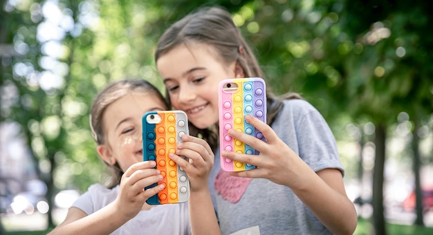Małe dziewczynki używają telefonów w modnych etui, aby przeciwdziałać stresowi.