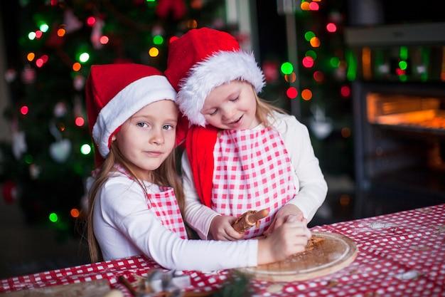 Małe dziewczynki w czapkach mikołaja pieczą piernikowe ciasteczka na boże narodzenie