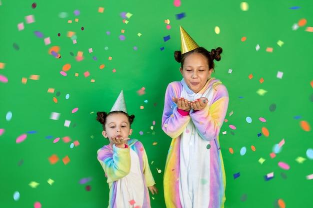 Małe dziewczynki w jasnych kostiumach na zielonym tle