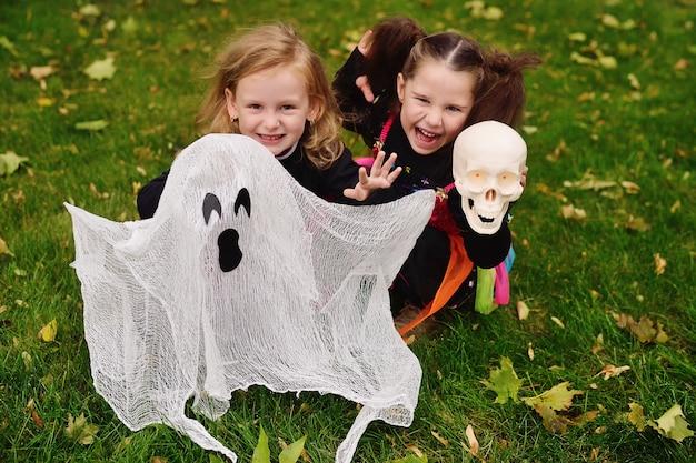 Małe dziewczynki w kostiumach na halloween czarownic na halloween z zabawkowym duchem w parku