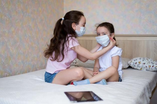 Małe dziewczynki w maskach ochronnych dopasowują się nawzajem w domu