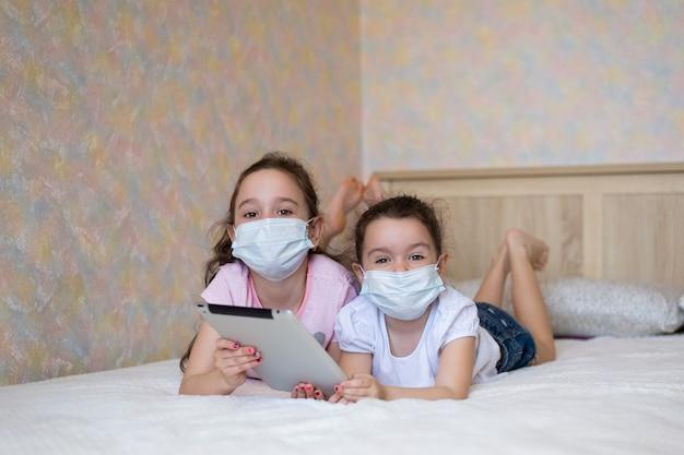 Małe dziewczynki w maskach ochronnych, grając na tablecie