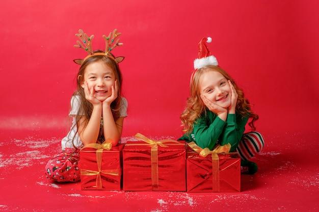 Małe dziewczynki w piżamach na czerwonym tle ze śmiejącymi się prezentami