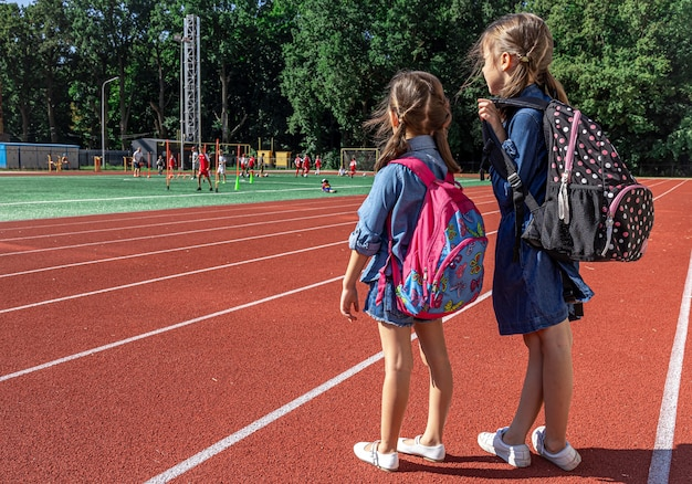 Małe dziewczynki w wieku szkolnym z plecakami na stadionie, obserwujące chłopców grających w piłkę nożną.