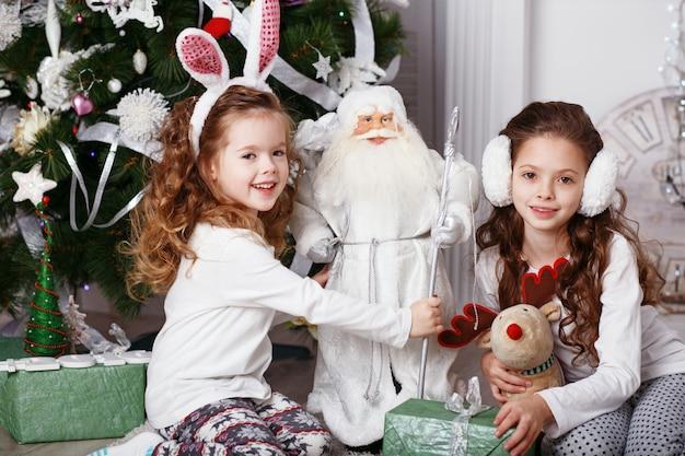 Małe dziewczynki w wygodne domowe ubrania, siedząc na podłodze