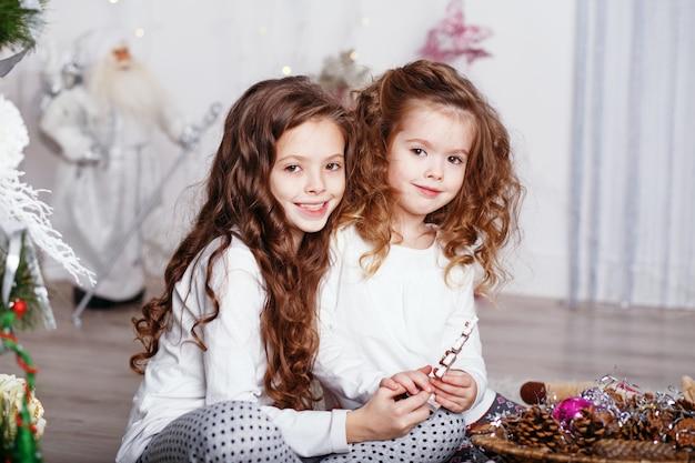Małe dziewczynki w wygodnych domowych ubraniach siedzi na podłodze w pięknych ozdób choinkowych
