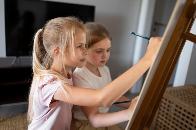 Małe dziewczynki wspólnie rysują sztalugami w domu