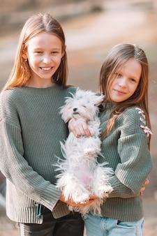 Małe dziewczynki z białym szczeniakiem. szczeniak w rękach dziewczynki