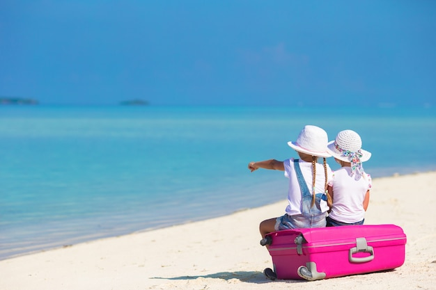 Małe dziewczynki z dużą walizką i mapą na tropikalnej plaży