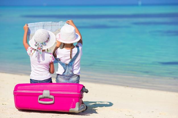 Małe dziewczynki z dużą walizką i mapą przy tropikalną plażą