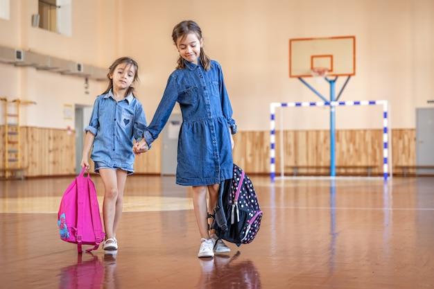 Małe dziewczynki z plecakami w pustej szkolnej sali gimnastycznej.