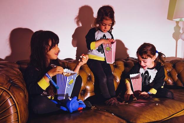 Małe dziewczynki z popcornem na kanapie