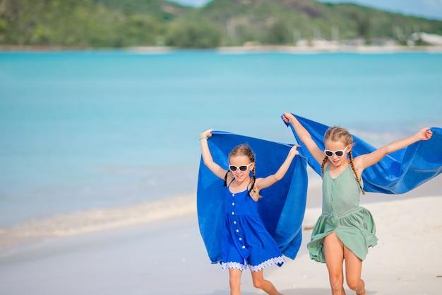 Małe dziewczynki zabawy ciesząc się wakacje na tropikalnej plaży