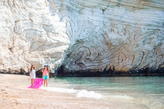 Małe dziewczynki zabawy na tropikalnej plaży podczas letnich wakacji, grając razem