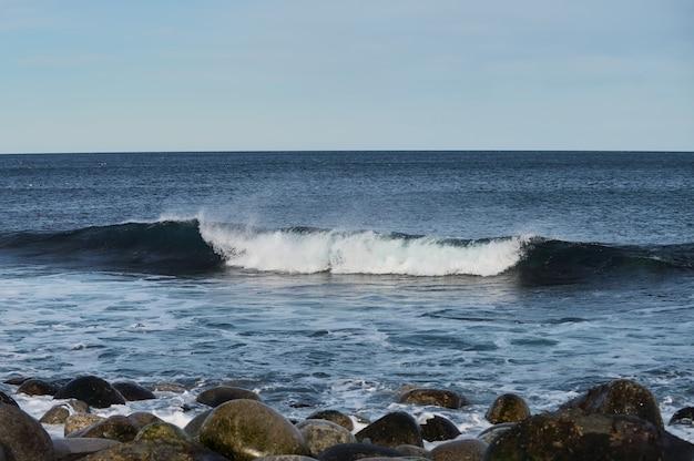 Małe fale morskie rozbijają się o kamienie na brzegu.