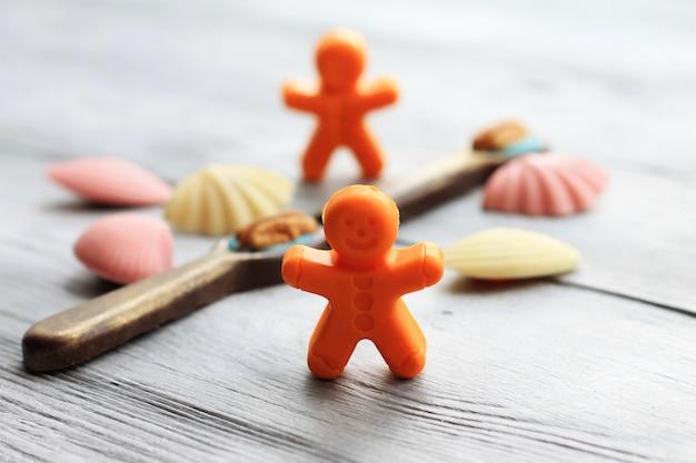 Małe figurki czekoladowe. łyżki, mali ludzie, muszle na drewnianym. słodka sztuka i jedzenie.