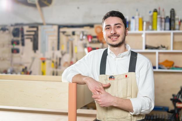 Małe firmy, koncepcja mebli i pracownika - przystojny młody mężczyzna pracujący w meblach