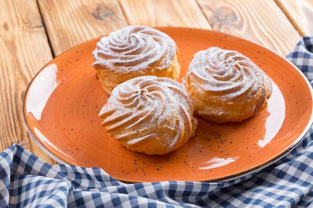 Małe francuskie ciasteczka profitroles z cukrem pudrem