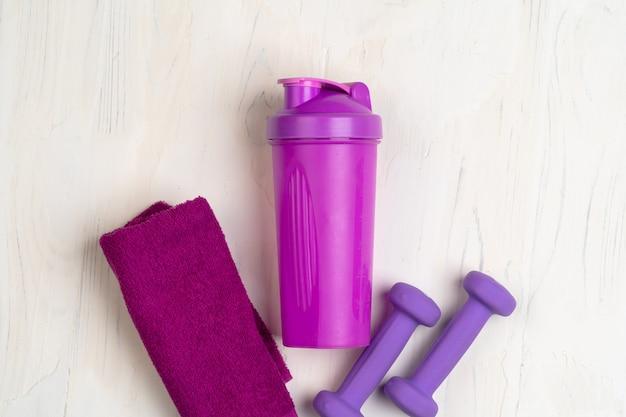 Małe hantle, shaker i ręcznik. koncepcja fitness