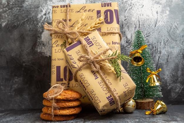 Małe i duże zapakowane prezenty stojące na ścianie oraz ciasteczka