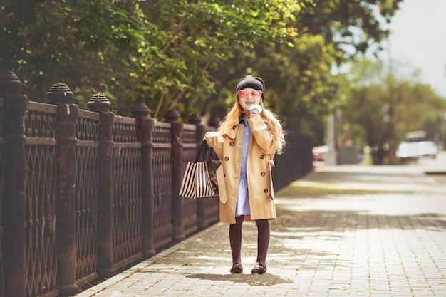 Małe i piękne dziecko dziewczynki słodkie i szczęśliwe z torbami na zakupy w rękach na ulicy