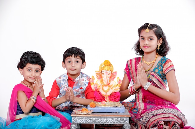 Małe indyjskie dzieci z panem ganeśą i modlącym się, hinduski festiwal ganesh