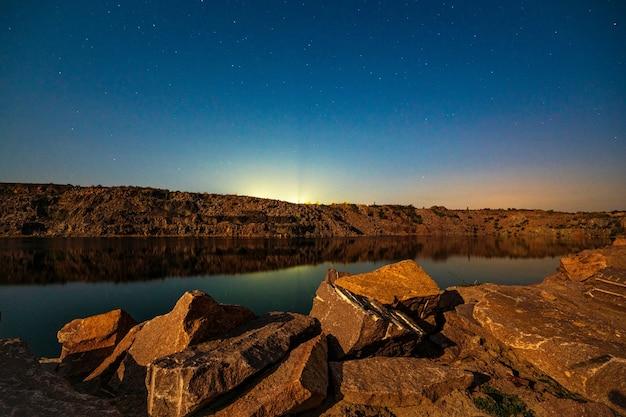 Małe jezioro otoczone kamiennymi odpadami z prac kopalnianych