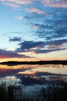Małe jezioro, w którym niebo i chmury o różnych kolorach odbijają się w słońcu, krajobraz