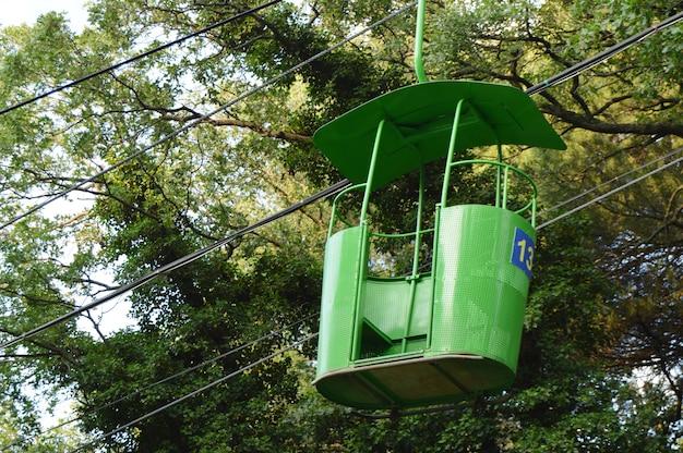 Małe kabiny dla pasażerów na kolejce linowej, na tle drzew