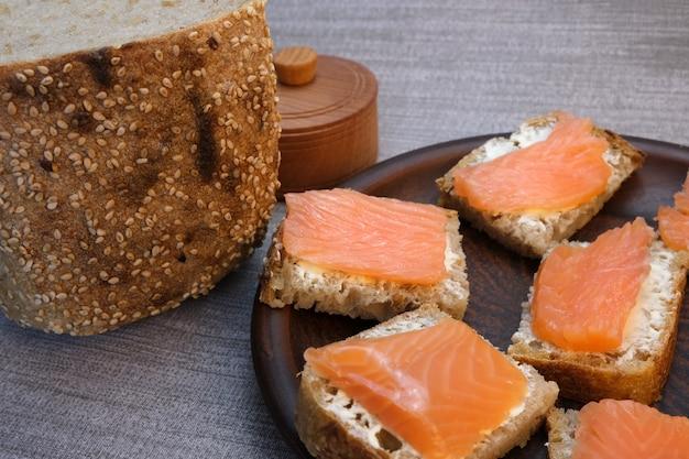Małe kanapki na chleb domowej roboty z masłem i czerwoną rybą