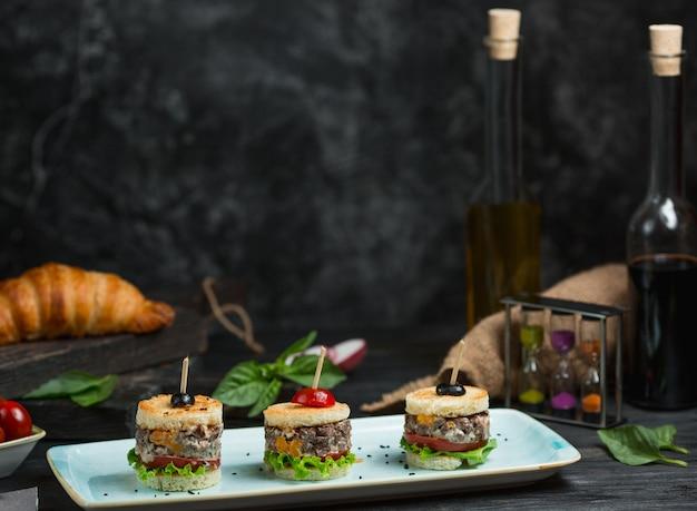 Małe kanapki na przyjęcie w białym kwadratowym talerzu
