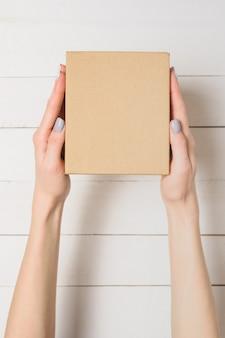 Małe kartonowe pudełko w rękach kobiet.