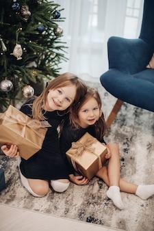 Małe kaukaskie dziewczynki patrzą na swoje prezenty w pobliżu choinki w domu i uśmiechają się razem