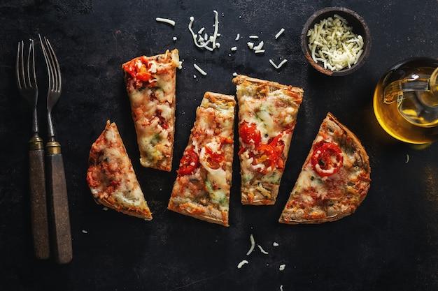 Małe kawałki pizzy z serem na ciemnym tle. widok z góry.
