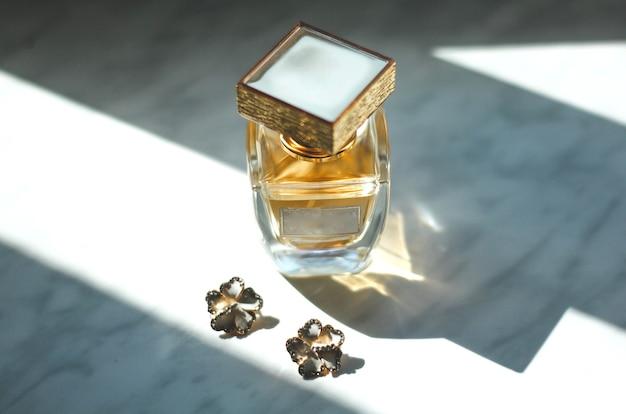 Małe kolczyki ślubne w kształcie kwiatów i stylowa flakonik perfum na szarym tle w promieniach słońca.