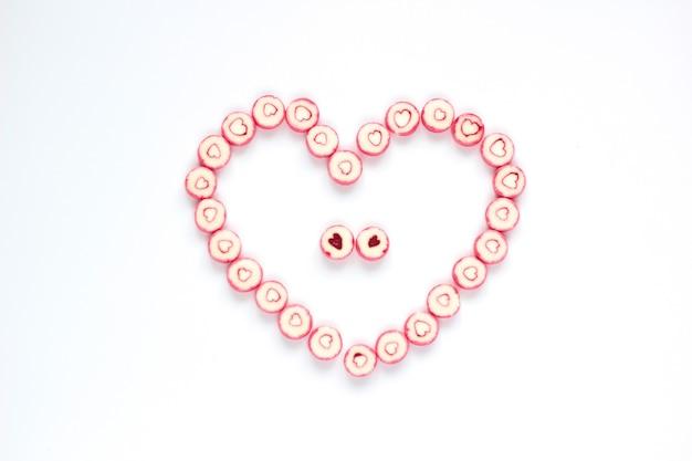 Małe kolorowe cukierki serca na białym tle