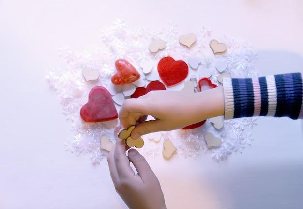 Małe kolorowe serduszka w rękach dziecka. proces dekoracji prezentów.