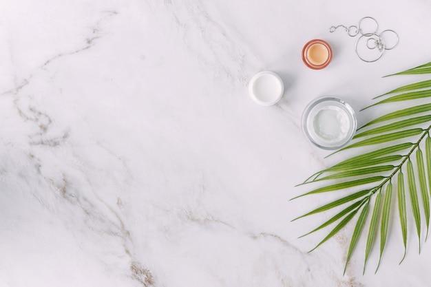 Małe kremowe butelki z damską biżuterią piękno liści palmy i koncepcja spa flat lay
