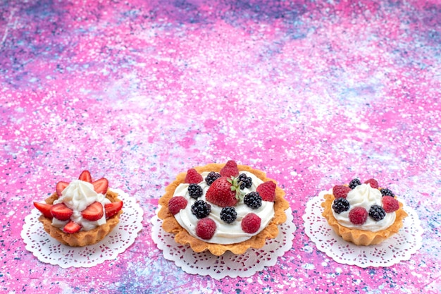 Małe kremowe ciasta z różnymi jagodami na jasnobiałym, słodko-jagodowym ciastku