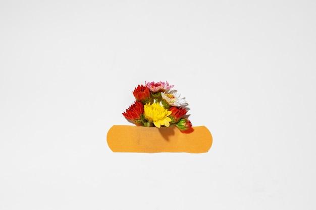 Małe kwiatki przyklejone samoprzylepną łatką na szarej płaskiej konstrukcji