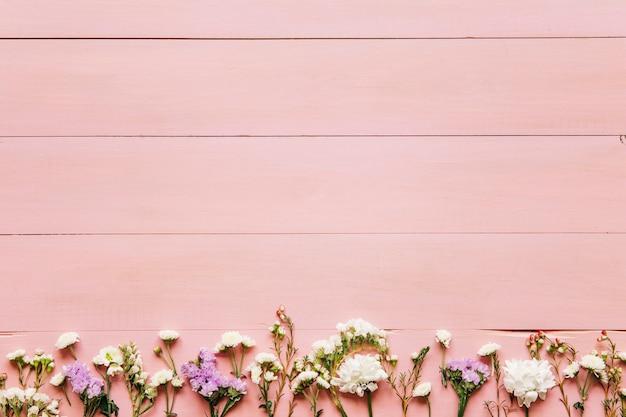 Małe kwiaty na różowym drewnianym stole