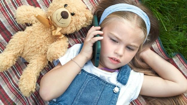 Małe ładne dziecko dziewczynka leżąc na kocu na zielonym trawniku latem z jej zabawką pluszowego misia rozmawia przez telefon komórkowy.