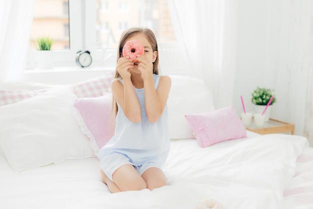 Małe ładne dziecko trzyma smaczne słodkie pączki, pozuje w sypialni na wygodnym łóżku