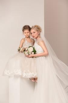 Małe ładne dziewczyny z kwiatami ubrane w suknie ślubne