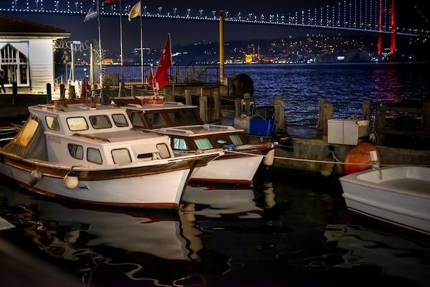 Małe łódki stojące na molo w nocy