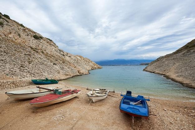 Małe łodzie do wynajęcia na wybrzeżu portu wśród wysokich skalistych brzegów przywiązanych do mola